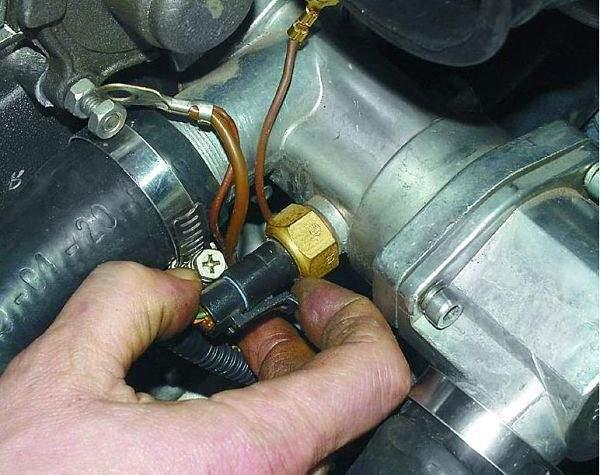 Чтобы проверить целостность проводки на ВАЗ-2110, 21102 нужно отсоединить колодку с проводами от датчика температуры охлаждающей жидкости и отжать пластмассовый зажим